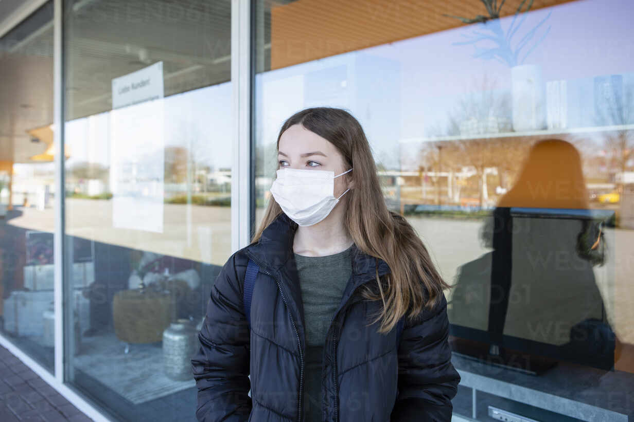 Girl with mask standing at closed shopping center - OJF00373 - Julia Otto/Westend61