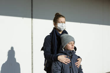 Woman wearing mask standing with son in front of a white wall, eyes closed - OJF00376