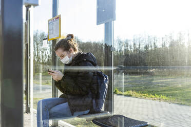 Girl with mask waiting at bus stop, using smartphone - OJF00379