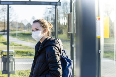 Portrait of a girl with mask waiting at bus stop - OJF00382