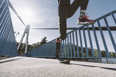Low section of disabled athlete with leg prosthesis running on a bridge - DAMF00308