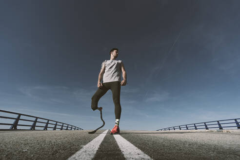 Disabled athlete with leg prosthesis standing on a road - DAMF00314