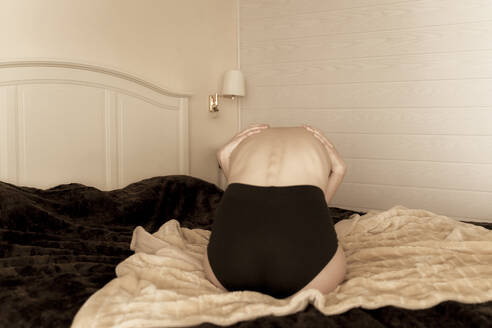 Rear view of young woman huddled on the bed at home - AFVF05962