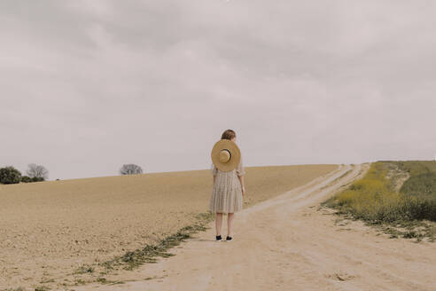 Woman with straw hat and vintage dress alone at a remote field road in the countryside - ERRF03068