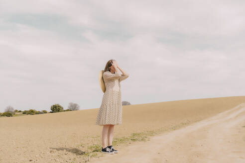 Woman in vintage dress alone at a remote field in the countryside covering her eyes - ERRF03074