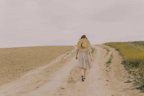 Woman with straw hat and vintage dress walking on a remote field road in the countryside - ERRF03080
