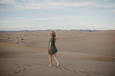 Back view of blond woman walking on sand dune, Algodones Dunes, Brawley, USA - LHPF01220