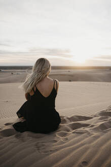 Back view of blond woman sitting on sand dune watching sunset, Algodones Dunes, Brawley, USA - LHPF01223