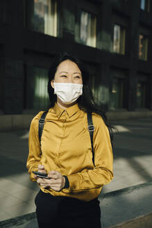 Happy woman with face mask holding smartphone - MASF17316