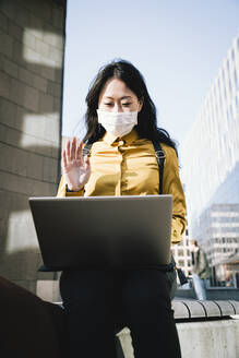 Businesswoman with face mask waving during video chat - MASF17328