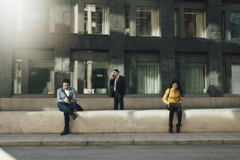 Three people keeping social distancing working outdoors - MASF17337