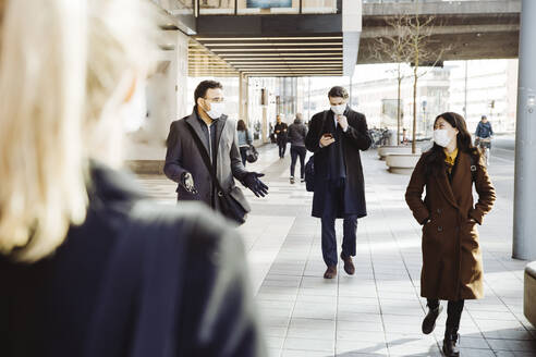 Business people wearing face mask walking in street - MASF17346