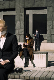 Business people with face masks keeping social distance - MASF17352