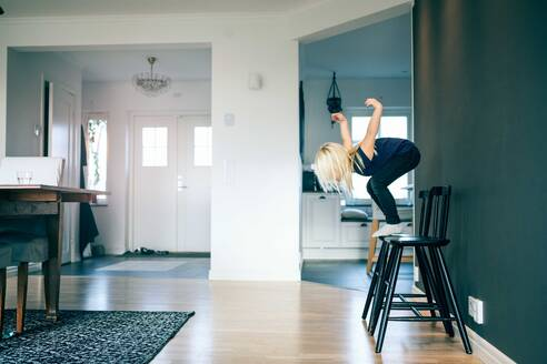 Side view of girl jumping from chair in living room at home - MASF17451