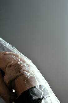 Midsection Of Shirtless Woman Wrapped In Plastic Against Gray Background - EYF03004