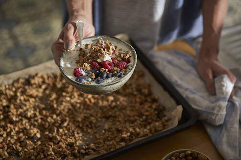 Woman's hand holding bowl of granola with yoghurt and berries - AUF00315