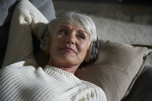 Portrait of senior woman relaxing on couch listening music with headphones - AUF00318