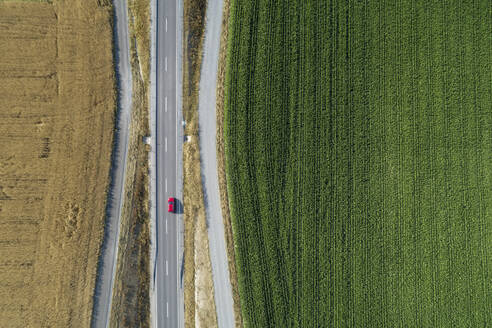 Germany, Bavaria, Drone view of country road cutting through green and yellow countryside fields in summer - RUEF02714