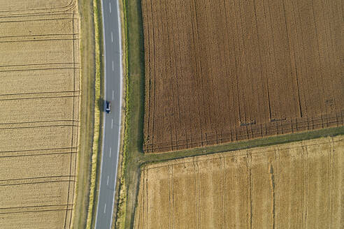 Germany, Bavaria, Drone view of country road cutting through brown and yellow countryside fields in summer - RUEF02717