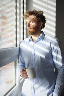Portrait of businessman holding coffee mug looking out of window - RBF07311