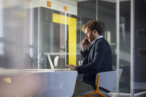 Businessman sitting at desk in office using laptop and smartphone - RBF07317
