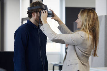 Businesswoman applying VR glasses on businessman in office - RBF07326