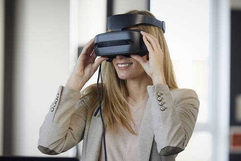 Smiling businesswoman wearing VR glasses in office - RBF07332