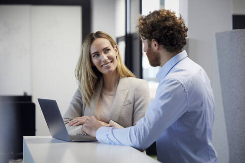 Businessman and businesswoman working together with laptop in office - RBF07335