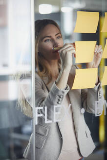 Businesswoman writing on adhesive notes on glass pane in office - RBF07344