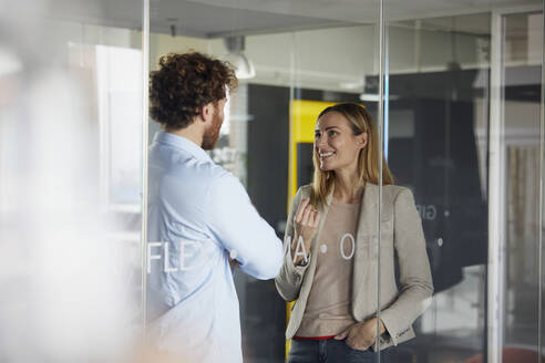 Businessman and businesswoman talking in office - RBF07347