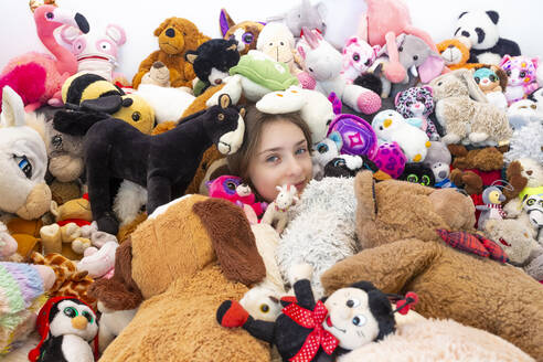 Girl sitting on couch, covered in cuddly toys - SARF04518