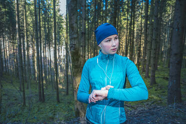 Young female jogger checking the time and looking sideways in the woods - VTF00620
