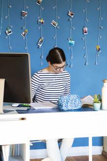 Portrait of girl sitting at desk at home doing homework - LVF08747