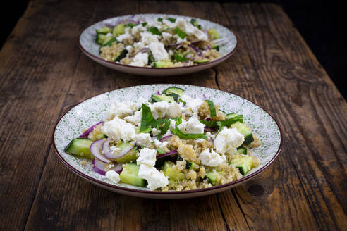 Two plates of vegetarian salad with cucumbers, quinoa, feta cheese, red onions and mint - LVF08753