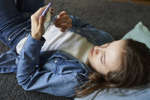 Girl lying on the floor at home looking at smartphone - AUF00337