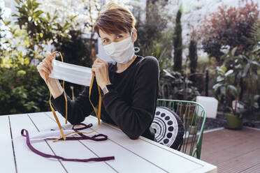 Woman sitting in garden, showing self-made face masks - MFF05390