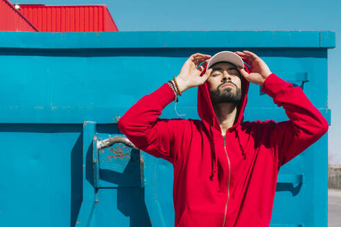 Young man wearing red hoodie, facing the sun - ERRF03116