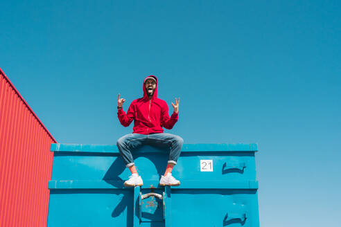 Young man wearing red hoodie, sitting on edge of blue container, making sign of the horns - ERRF03119