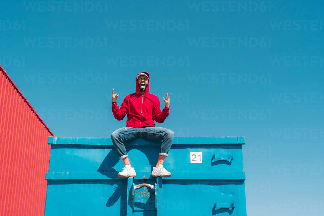Young man wearing red hoodie, sitting on edge of blue container, making sign of the horns - ERRF03119 - Eloisa Ramos/Westend61