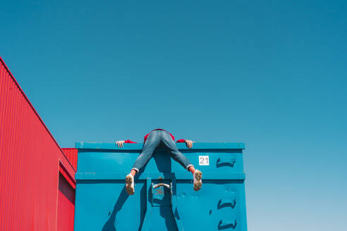 Young man hanging over edge of blue container, rear view - ERRF03122