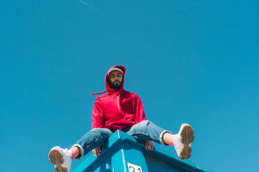 Young man sitting on edge of blue container, wearing read jacket - ERRF03125