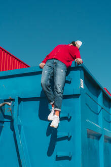 Young man relaxing on blue container, leaning backwards over edge - ERRF03128
