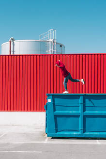 Young man wearing red hooded jacket balancing on edge of container in front of red wall in industrial setting - ERRF03131