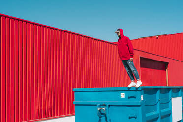 Young man wearing red hooded jacket standing on edge of container in front of red wall - ERRF03134
