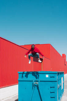 Young man wearing red hooded jacket jumping from edge of container in front of red wall - ERRF03137