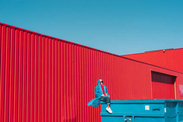 Young man wearing rain coat sitting on edge of blue container in front of red wall, looking up - ERRF03140