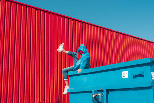 Young man wearing rain coat sitting on edge of blue container in front of red wall, raising leg - ERRF03146