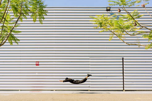 Man wearing black overall in the air in front of industrial building - ERRF03155
