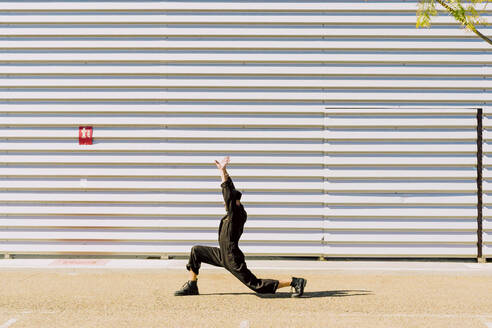 Man wearing black overall performing in front of industrial building - ERRF03161