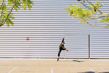 Man wearing black overall jumping in the air in front of industrial building - ERRF03170